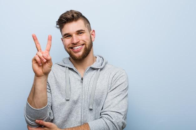 Giovane uomo bello di forma fisica che mostra numero due con le dita.