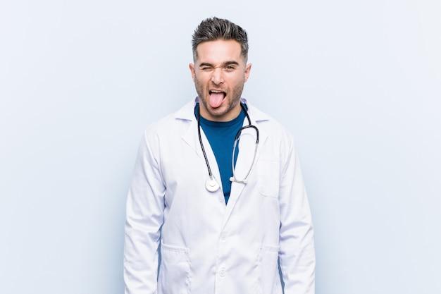 Giovane uomo bello di medico divertente e amichevole che attacca fuori lingua.