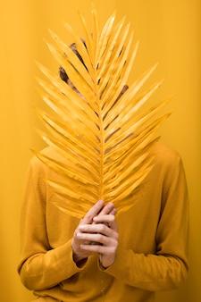 Giovane uomo bello dietro foglia di palma in una scena gialla