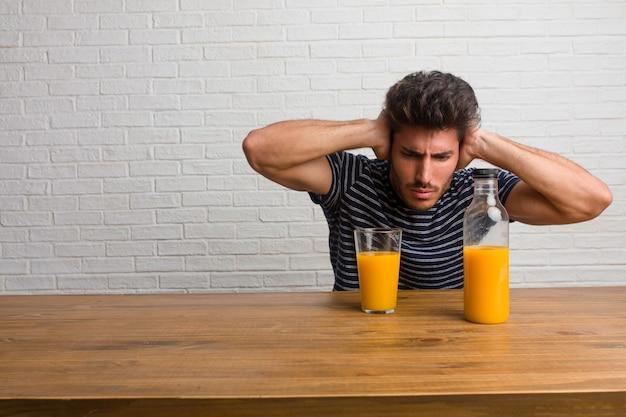 Giovane uomo bello e naturale che si siede su un tavolo che copre le orecchie con le mani