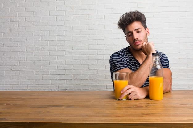 Giovane uomo bello e naturale che si siede su un tavolo che dubita e confuso