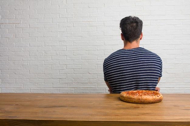 Giovane uomo bello e naturale che si siede su un tavolo che mostra indietro, in posa e in attesa