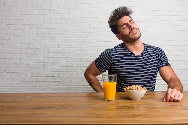 Giovane uomo bello e naturale, seduto su un tavolo con dolore alla schiena a causa di stress da lavoro