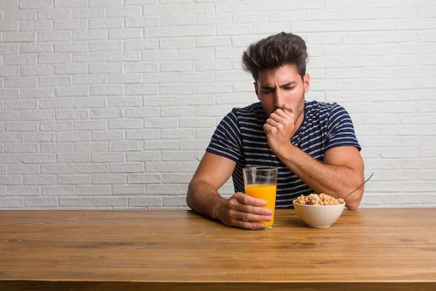 Giovane uomo bello e naturale, seduto su un tavolo con un mal di gola, malato a causa di un virus