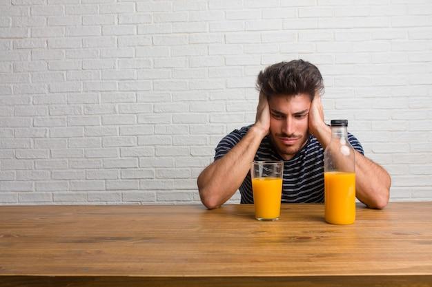 Giovane uomo bello e naturale, seduto su un tavolo frustrato e disperato, arrabbiato e triste con le mani sulla testa. fare colazione, include succo d'arancia e una ciotola di cereali.