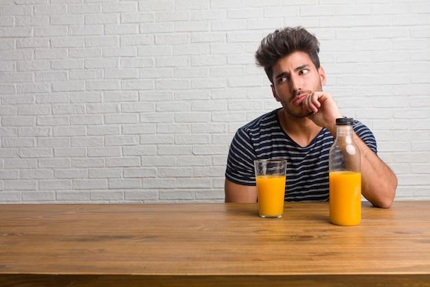 Giovane uomo bello e naturale seduto su un tavolo in dubbio e confuso, pensando a un'idea o preoccupato per qualcosa.