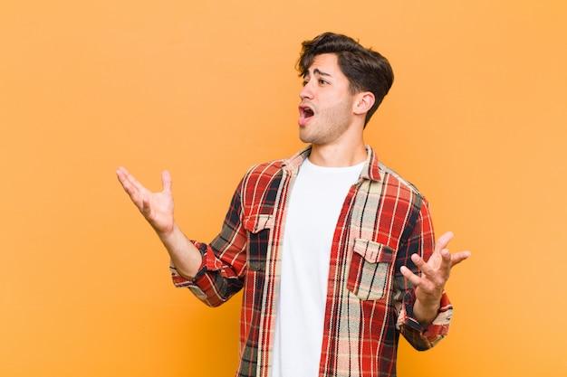 Giovane uomo bello esibirsi in un'opera o cantare in un concerto o uno spettacolo, sentirsi romantico, artistico e appassionato sulla parete arancione