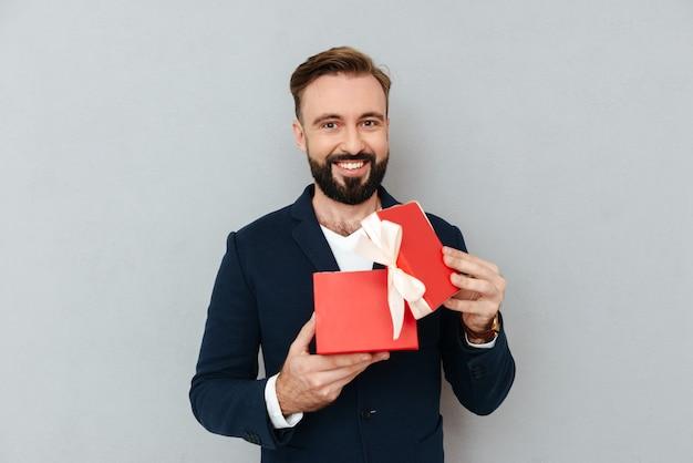 Giovane uomo bello felice che esamina regalo rosso isolato