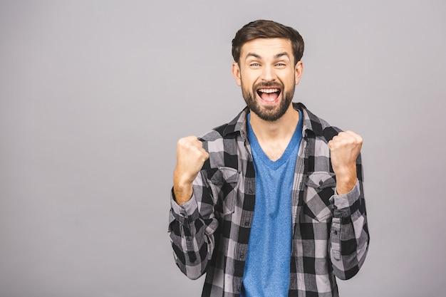 Giovane uomo bello felice che gesturing e che tiene bocca aperta mentre stando contro la parete bianca grigia.