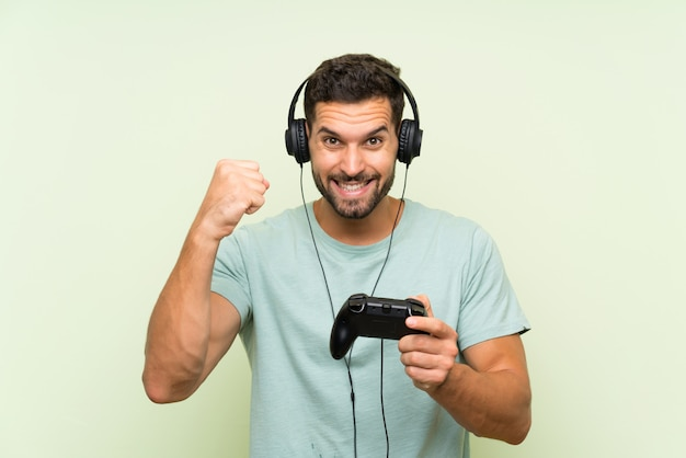 Giovane uomo bello fortunato che gioca con un controller di videogioco