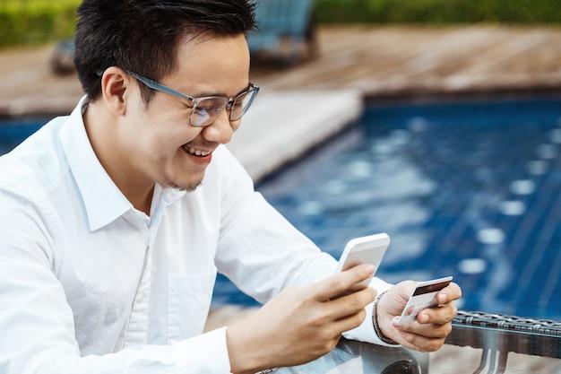 Giovane uomo bello godere shopping online sul cellulare con carta di credito.