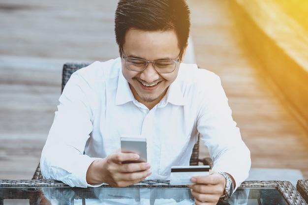 Giovane uomo bello godere shopping online sul telefono cellulare con carta di credito.
