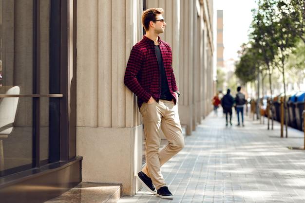 Giovane uomo bello hipster in posa sulla strada europea, colori dai toni caldi e soleggiati, vestiti alla moda casual, umore di viaggio