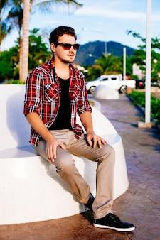 Giovane uomo bello hipster rilassato al giorno pieno di sole sul parco dell'isola