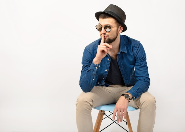 Giovane uomo bello hipster, sfondo bianco isolato studio, vestito elegante, camicia di jeans, pantaloni, cappello, occhiali da sole, seduto sulla sedia, dito sulle labbra, gesto di silenzio, espressione, emozione