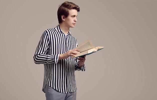 Giovane uomo bello in camicia a strisce che legge un libro su fondo grigio