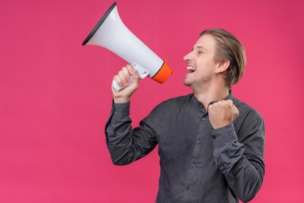 Giovane uomo bello in camicia nera che grida al megafono