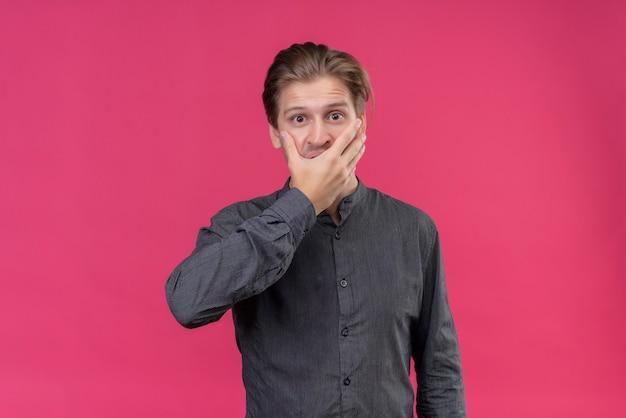 Giovane uomo bello in camicia nera che sembra scioccato che copre la bocca con la mano