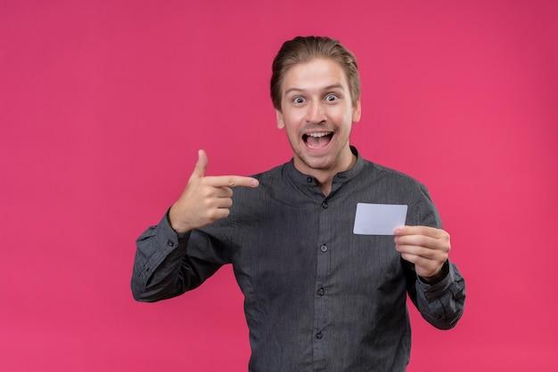 Giovane uomo bello in camicia nera che tiene il telefono cellulare che punta con il dito ad esso