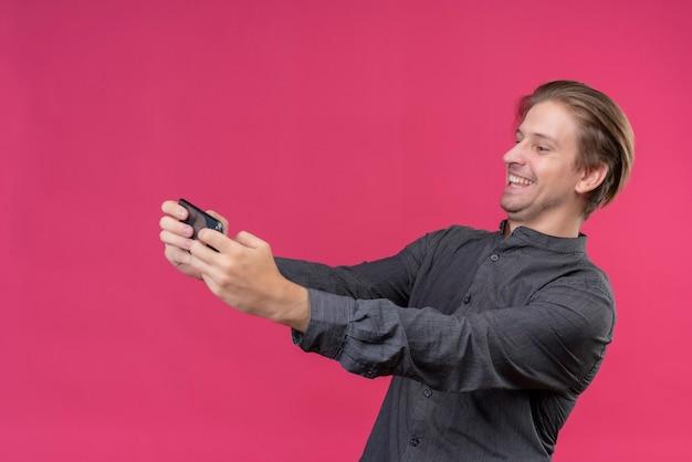 Giovane uomo bello in camicia nera che tiene il telefono cellulare prendendo selfie