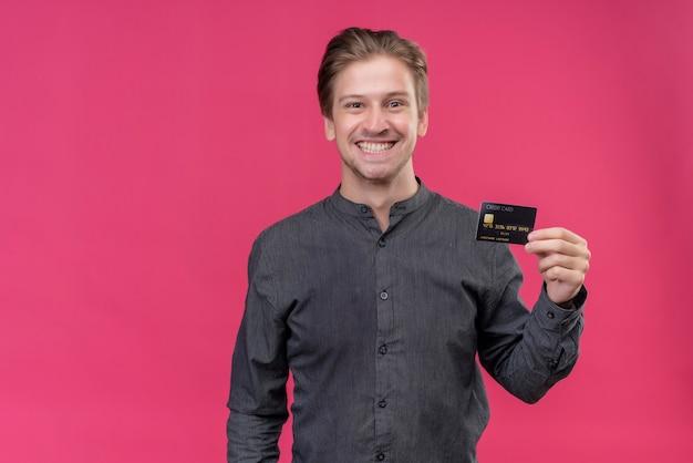 Giovane uomo bello in camicia nera che tiene la carta di credito