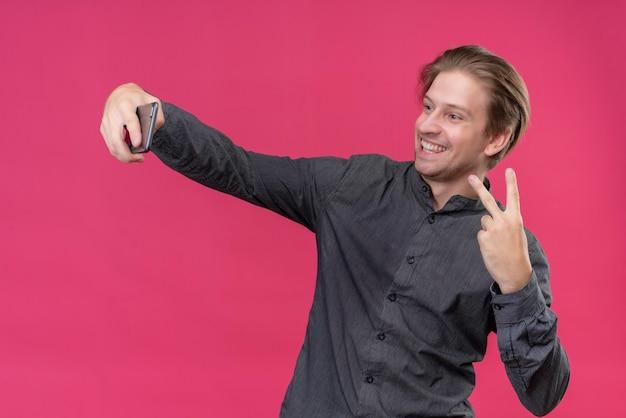 Giovane uomo bello in camicia nera che tiene selfie prendendo mobile