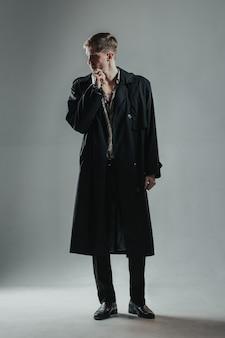 Giovane uomo bello in mantello nero che osserva da parte con l'espressione del pensiero.