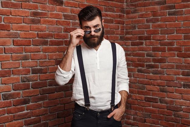 Giovane uomo bello in occhiali da sole che posano sul muro di mattoni.