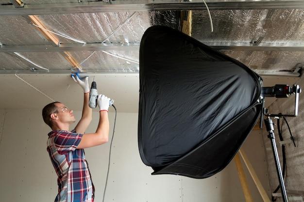 Giovane uomo bello in occhiali e guanti da lavoro che fissano il controsoffitto del muro a secco al telaio metallico sul soffitto isolato con un foglio di alluminio davanti alla scatola morbida
