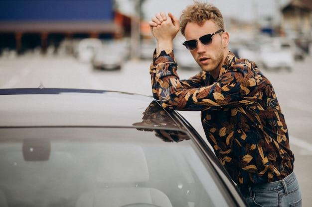 Giovane uomo bello in piedi in auto