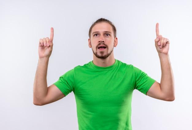 Giovane uomo bello in t-shirt verde che punta le dita in alto guardando fiducioso avendo una grande idea in piedi su sfondo bianco
