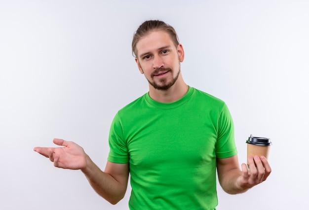 Giovane uomo bello in t-shirt verde tenendo la tazza di caffè guardando fiducioso alzando la mano in piedi su sfondo bianco