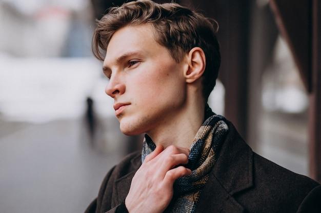 Giovane uomo bello in un cappotto fuori strada