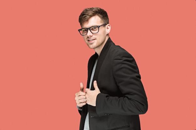 Giovane uomo bello in vestito nero e vetri isolati sulla parete rossa