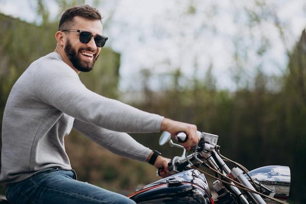 Giovane uomo bello in viaggio in moto