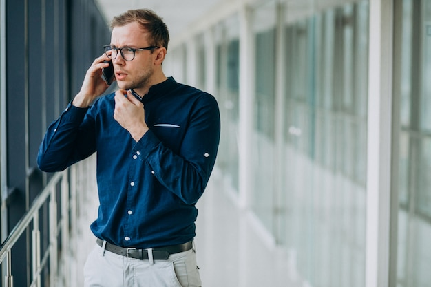 Giovane uomo bello parlare al telefono in ufficio
