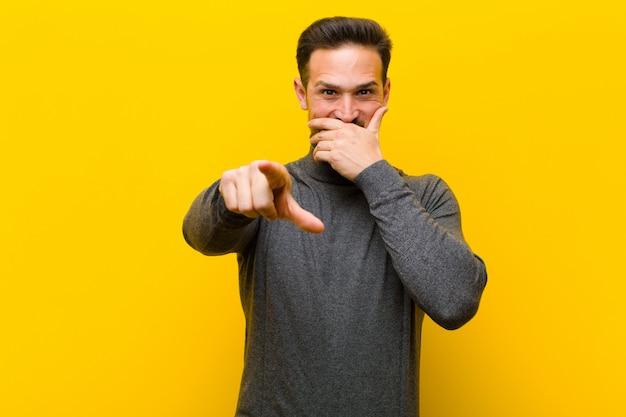 Giovane uomo bello ridere di te, indicando la fotocamera e prendendo in giro o deridendoti contro il muro arancione