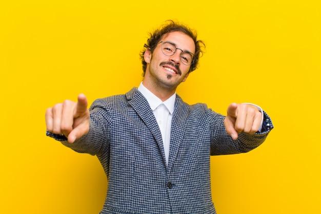 Giovane uomo bello sentirsi felice e fiducioso, indicando la fotocamera con entrambe le mani e ridendo, scegliendo il muro arancione