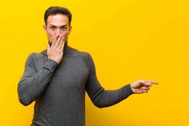Giovane uomo bello sentirsi felice, scioccato e sorpreso, coprendosi la bocca con la mano e indicando lo spazio laterale della copia contro la parete arancione