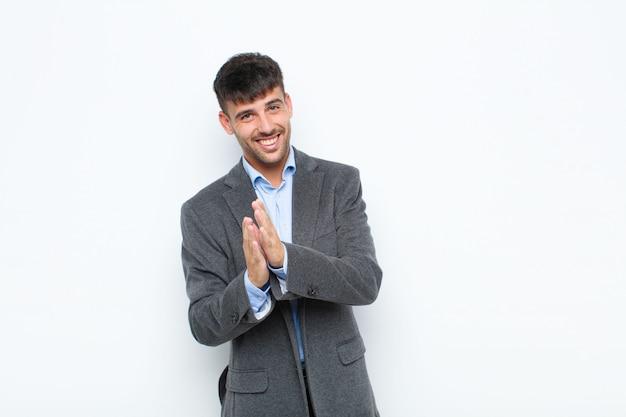 Giovane uomo bello sentirsi felici e di successo, sorridendo e battendo le mani, dicendo congratulazioni con un applauso contro il muro bianco