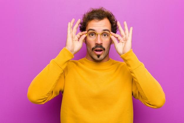 Giovane uomo bello sentirsi scioccato, stupito e sorpreso, con gli occhiali con uno sguardo stupito e incredulo contro il muro viola