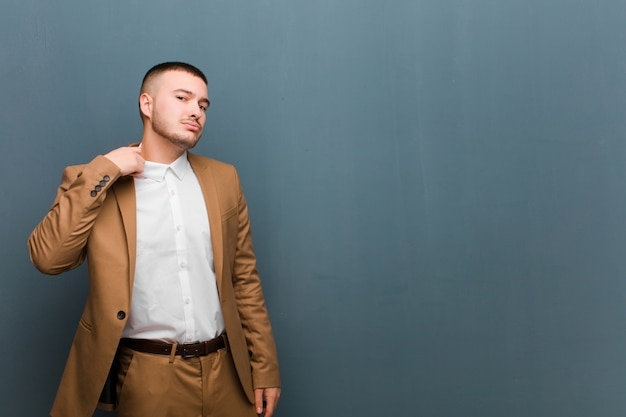 Giovane uomo bello sentirsi stressato, ansioso, stanco e frustrato, tirando il collo della camicia, sembrando frustrato dal problema sul muro
