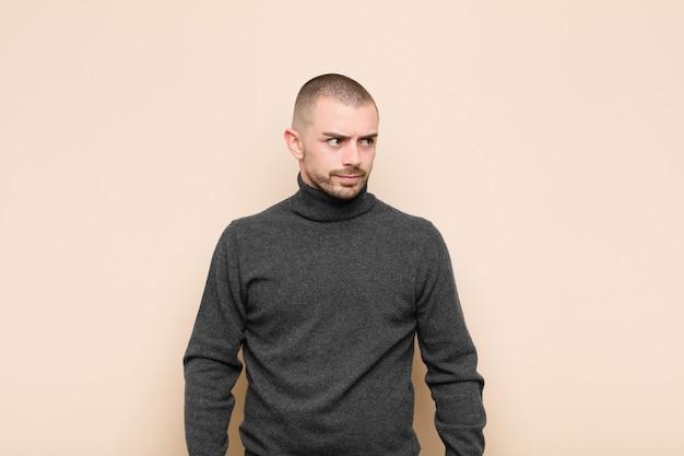 Giovane uomo bello sentirsi triste, arrabbiato o arrabbiato e guardando al lato con un atteggiamento negativo, accigliato in disaccordo sul muro