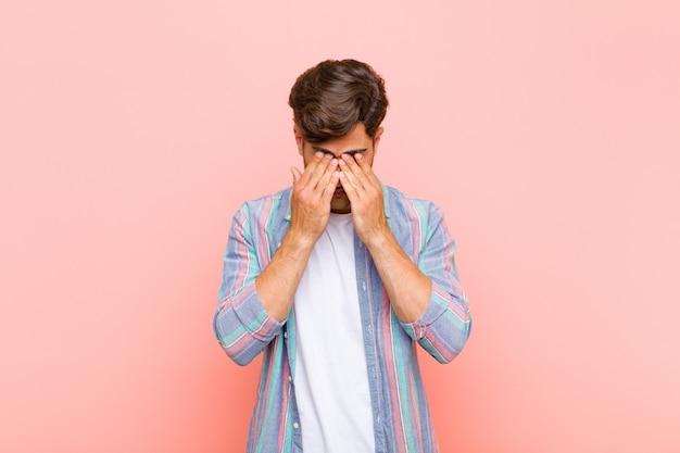 Giovane uomo bello sentirsi triste, frustrato, nervoso e depresso, coprendosi il viso con entrambe le mani, piangendo contro il muro rosa