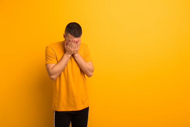 Giovane uomo bello sentirsi triste, frustrato, nervoso e depresso, coprendosi il viso con entrambe le mani, piangendo contro la parete piatta