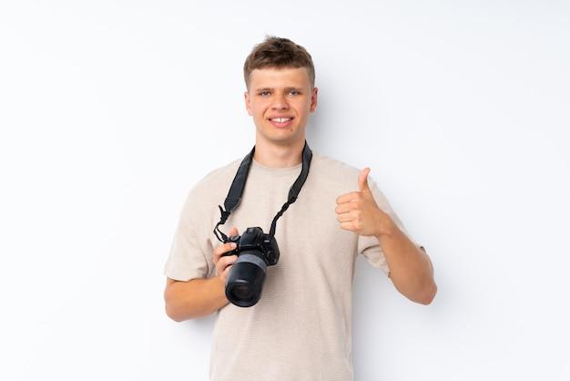 Giovane uomo bello sopra bianco isolato con una macchina fotografica professionale e con il pollice in su
