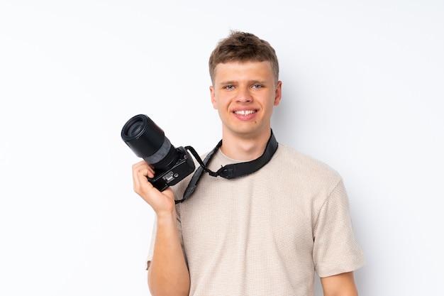 Giovane uomo bello sopra bianco isolato con una macchina fotografica professionale