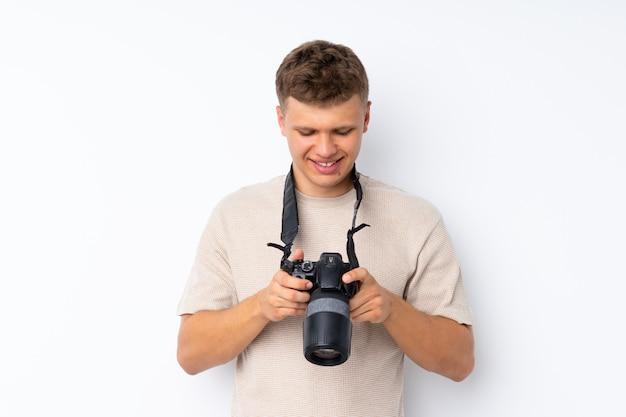 Giovane uomo bello sopra fondo bianco isolato con una macchina fotografica professionale