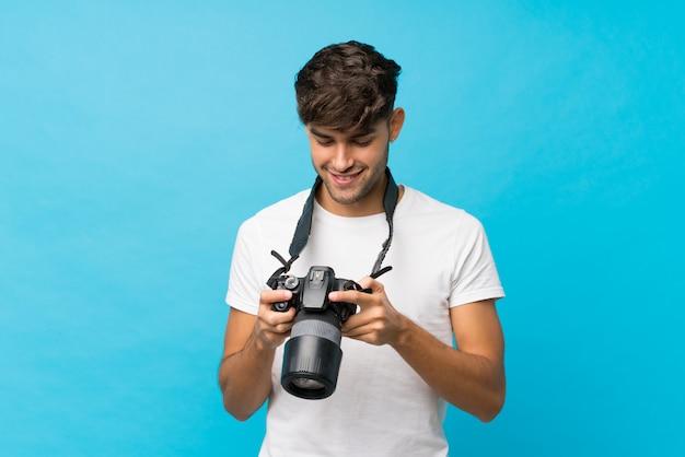 Giovane uomo bello sopra fondo blu isolato con una macchina fotografica professionale