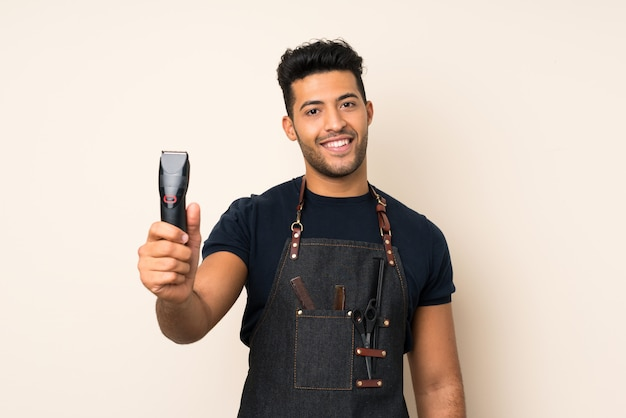 Giovane uomo bello sopra fondo isolato con il parrucchiere o il vestito da barbiere e la tenuta della tagliatrice dei capelli